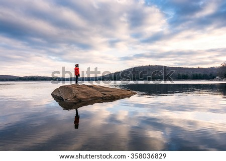 Boy standing on a rock island - stock photo