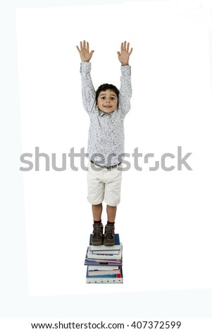 Boy standing on a stack of books isolated on white background - stock photo