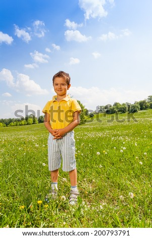 Boy standing on green grass holding his hands