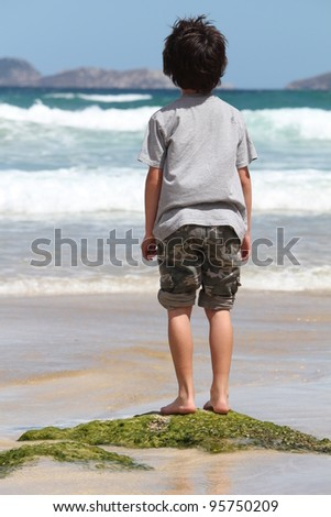 Boy standing on rock watch watching the ocean waves - stock photo