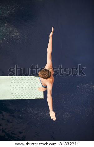 Boy standing on springboard - stock photo