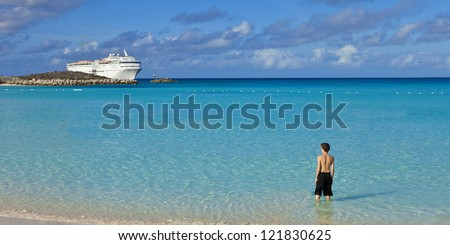 boy standing on tropical bahamian beach with cruise ship in background - stock photo
