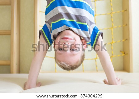 Boy standing upside down on his hands in gym class. Selective focus on a child's face - stock photo