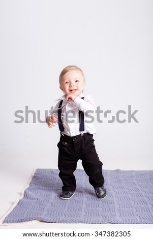 Boy stands on blue blanket on white background