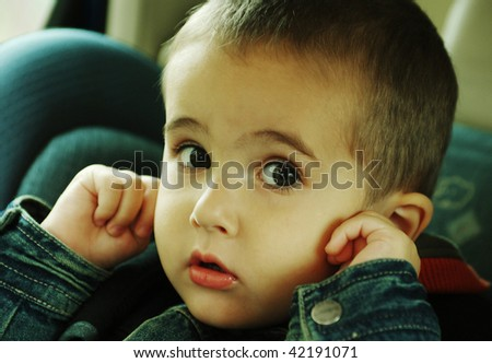 Boy stops up his ears with fingers avoiding loud sound of traffic in the car - stock photo