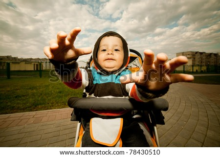 Boy stretches his arms forward while sitting in a baby carriage