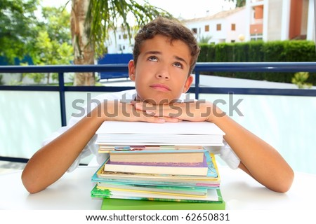 boy student teenager bored thinking with books stacked outdoors - stock photo