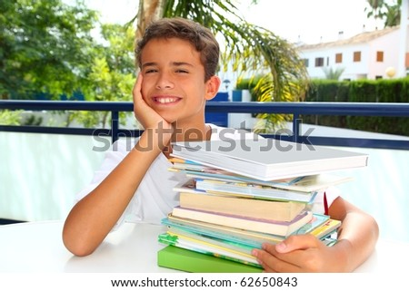boy student teenager happy thinking with books stacked outdoors - stock photo