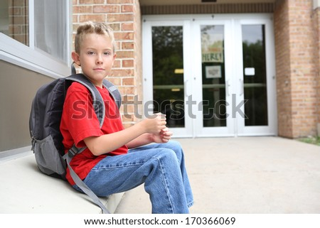 Boy student waiting outside of school - stock photo