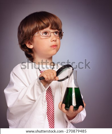 boy studying a chemistry substance in a test tube with a magnifying glass - stock photo
