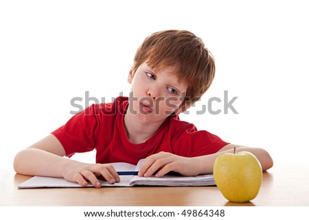 boy studying and distracted with an apple