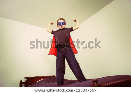 Boy superhero showing his muscles - stock photo