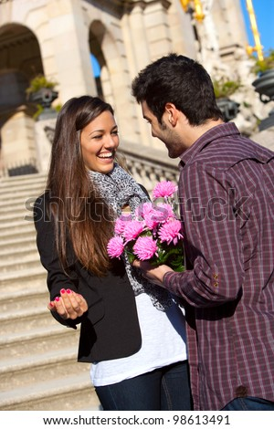 Boy surprising his cute girlfriend with pink flowers on date outdoors. - stock photo