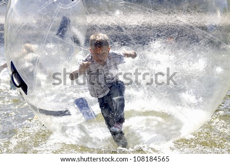 Boy Swim inside pastic bubble - stock photo