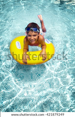 boy swimming in pool on rubber ring, retro toned - stock photo