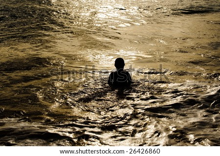 Boy swimming in the pacific ocean - stock photo
