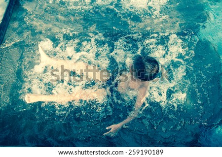 Boy swimming in the pool outdoor - stock photo