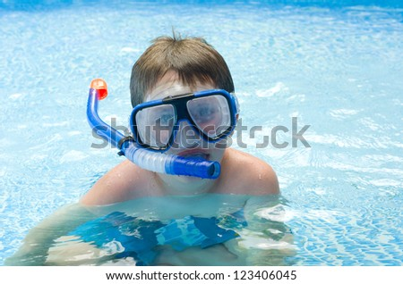Boy swimming with mask and snorkel in pool - stock photo