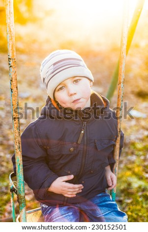 Boy swinging on a swing in a sunny autumn day
