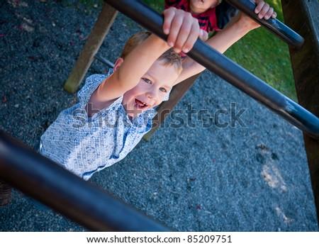 Boy swinging on monkey bars - stock photo