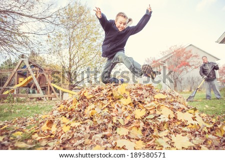 Boy taking a break from chores to jump in the leaves - stock photo