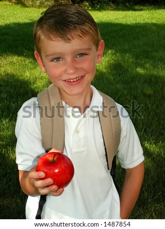 boy taking an apple for his teacher on the first day of school - stock photo