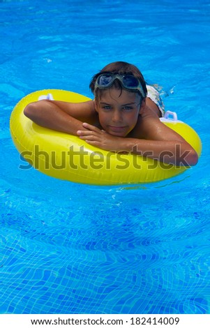 boy taking sunbath in blue pool on rubber ring - stock photo