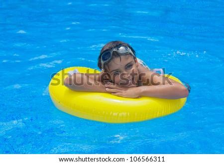 boy taking sunbath in pool on rubber ring - stock photo