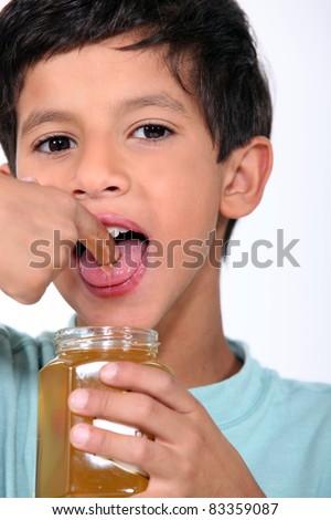 Boy tasting some honey - stock photo