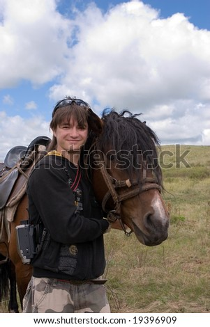 Boy teen and horse at summer day in prairie - stock photo