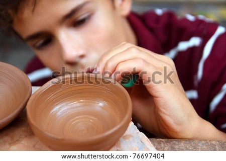 boy teen potter clay bowl working in pottery workshop traditional arts - stock photo