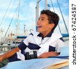 boy teen sailor laying on marina boat chart map smiling in summer vacation - stock photo