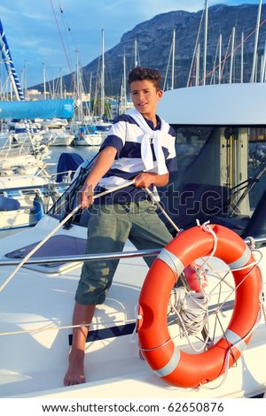 Boy teen sailor mooring boat rope in harbor summer marina standing up - stock photo