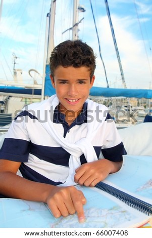 boy teen sailor sitting on marina boat chart map smiling in summer vacation - stock photo