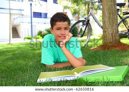 boy teen student homework laying green grass garden bicycle background - stock photo