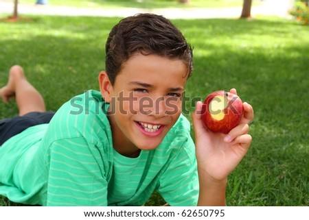boy teenager eating red apple laying on garden grass outdoors - stock photo