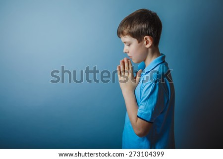 boy teenager European appearance in a blue shirt brown hair hung his head closed his eyes on a gray background, prayer - stock photo