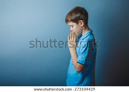 boy teenager European appearance in a blue shirt brown praying closed his eyes lowered his head on a gray background, faith, hope, - stock photo