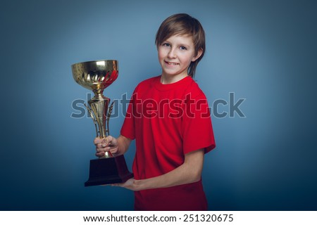 boy teenager European appearance in a red shirt holding a cup on a gray background, the reward cross process - stock photo