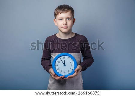 boy teenager European appearance in brown sweater holding a blue clock time five minutes to twelve on a gray background, clock - stock photo