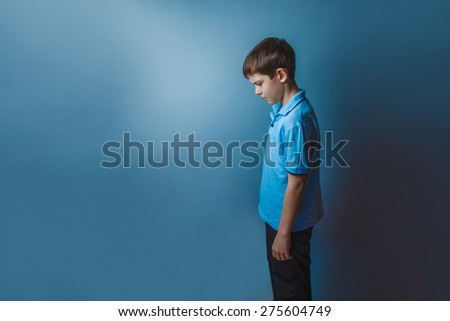Boy teenager European appearance ten years standing sideways looks down on a gray background - stock photo