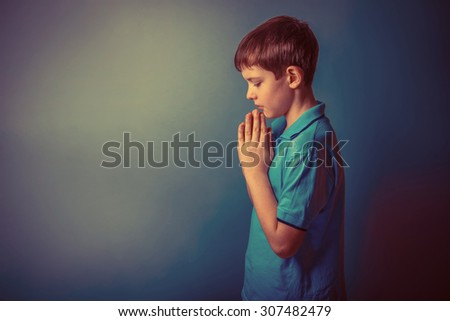 Boy teenager European appearance ten years stands sideways praying on a gray background retro - stock photo