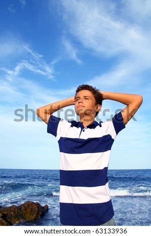 boy teenager hands in head relaxed in blue ocean sea beach summer vacation - stock photo