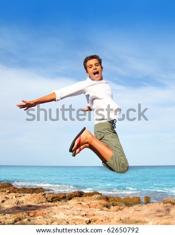 boy teenager high fly jump on beach blue sky summer vacation - stock photo