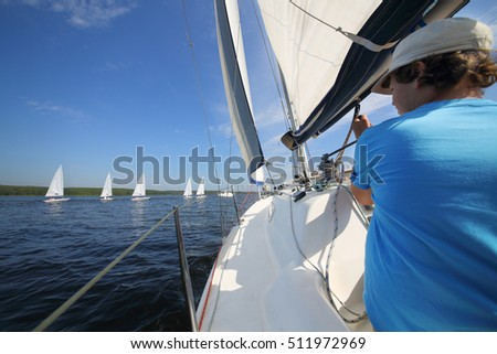 Boy teenager in cap sails on yacht on river near other sailboats at summer sunny day, back view