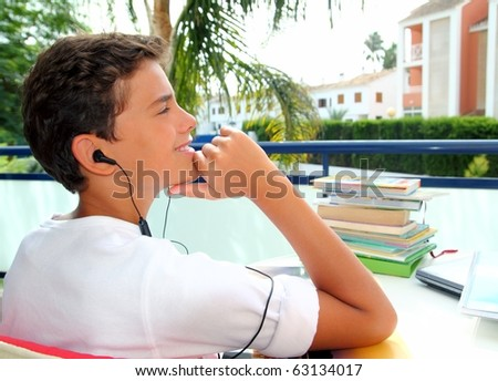 Boy teenager relaxed outdoor earphones hearing music in garden - stock photo