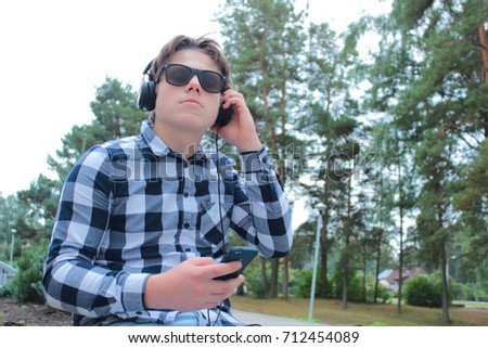 Boy teenager (schoolboy or student) in a shirt, smiling in sunglasses, listening to music on the phone, park background.