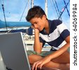 boy teenager seat on boat marina laptop computer summer vacation - stock photo