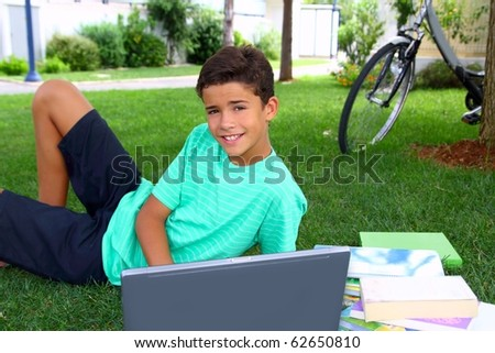 boy teenager student homework sitting grass garden laptop computer - stock photo
