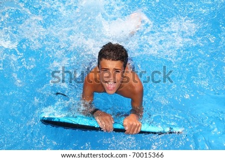 boy teenager surfboard splashing blue water happy in sea pool - stock photo